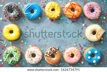 Festive carnival or birthday frame from various colourful donuts with confetti on rustical grey background #1626734791