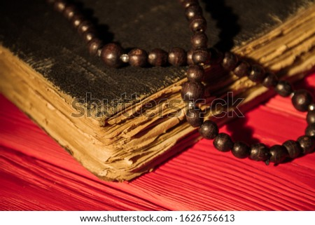 Old obsolete vintage book and brown bead necklace. Close-up. Red table background. #1626756613