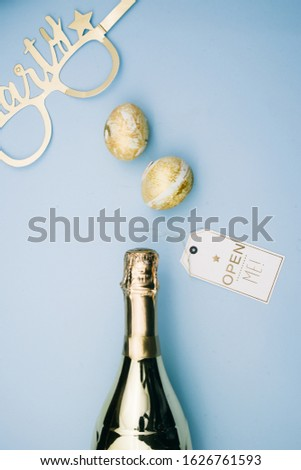 Party theme image, conceptual image with a bottle of champagne with open me card and party time fun glasses,on a blue background, top view,