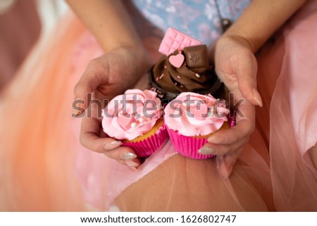 Cupcakes with beautifully decorated cream are held in hands by a girl in a beautiful dress and light manicure on a background of pink and blue clothes #1626802747