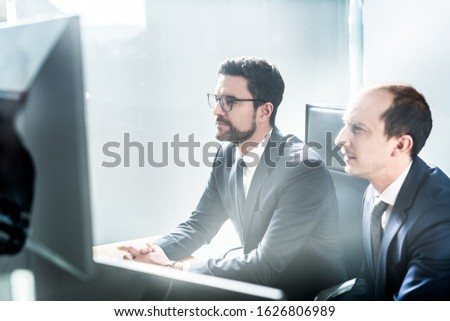 Image of two thoughtful businessmen looking at data on multiple computer screens, solving business issue at business meeting in modern corporate office. Business success concept. #1626806989