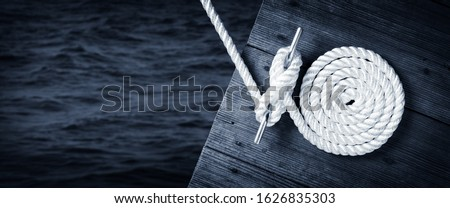 Boat Rope Secured To Cleat On Wooden Dock With Dark Water Below Royalty-Free Stock Photo #1626835303