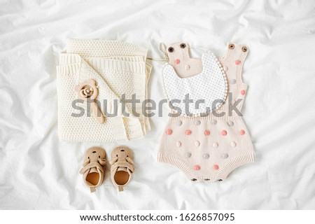 Set of kids clothes and accessories. Bodysuit, bib,  knitted blanket, baby boots and toy on bed. Flat lay, top view #1626857095