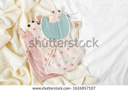 Pink bodysuit and  bib on knitted blanket. Set of  kids clothes and accessories  on bed. Fashion newborn. Flat lay, top view #1626857107