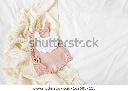 Pink bodysuit and  bib on knitted blanket. Set of  kids clothes and accessories  on bed. Fashion newborn. Flat lay, top view #1626857113