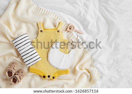 Yellow bodysuit, bib, baby boots and toy on knitted blanket. Set of  kids clothes and accessories  on bed. Fashion newborn. Flat lay, top view #1626857116