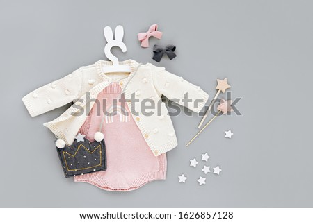 Pink bodysuit with knitted jumper, kids handbag shape of crown on cute hanger with bunny ears. Set of  baby clothes and accessories  on gray background. Fashion childs outfit. Flat lay, top view #1626857128