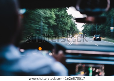 Selective focus on expressway autobahn road from car cockpit, male driving for crossing thruway interchange during automobile trip in rent transport, window view of interstate street freeway #1626870517