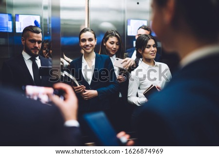 Reflection of group of amused smiling people in suits carrying documents and taking pictures with smartphone while standing together in elevator cabin at urban office building