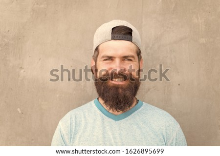 Beard divides the boys from the men. Happy caucasian guy wearing beard on grey wall. Bearded man smiling with stylish mustache and beard shape. Unshaven hipster with textured beard hair outdoor. #1626895699