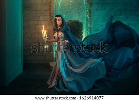 lady Queen woman medieval royal dress run escapes from Gothic night castle. Blue silk dress, cloak train plume waving motion. Holds in hands old candlestick burning candles. Background old retro room #1626914077