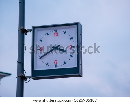 Street clock with a traditional dial and hands arrows for hours and minutes. An rectangular boxed analog clock on a city lighting pole shows the exact time 3:40 pm