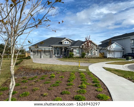 A stately residential home in a residential neighborhood with a curved paved driveway. Concept wealth and riches. #1626943297