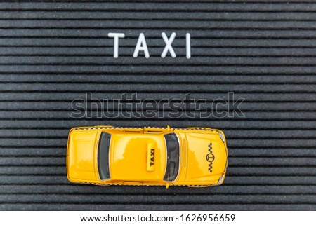 Simply design yellow toy car Taxi Cab model with inscription TAXI letters word on black background. Automobile and transportation symbol. City traffic delivery urban service idea concept. Copy space #1626956659
