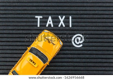 Simply design yellow toy car Taxi Cab model with inscription TAXI letters word on black background. Automobile and transportation symbol. City traffic delivery urban service idea concept. Copy space #1626956668