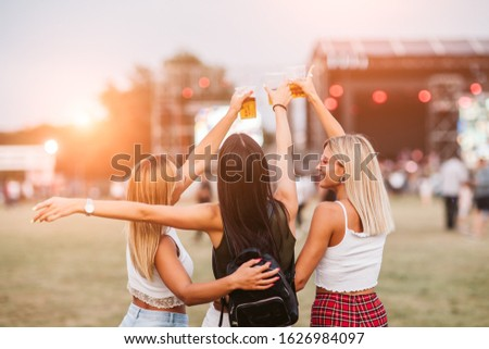 Back view of female friends toasting with beer #1626984097