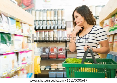 Confused female customer choosing food products on shelf in supermarket Royalty-Free Stock Photo #1627000549