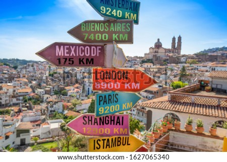 Panoramic view of Taxco historic city center with the signs indicating the distance to world capitals on the foreground #1627065340