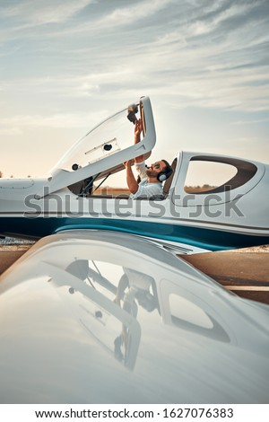 Pilot closes a cocpit and prepare to fly. Copyspace. Vertical photo