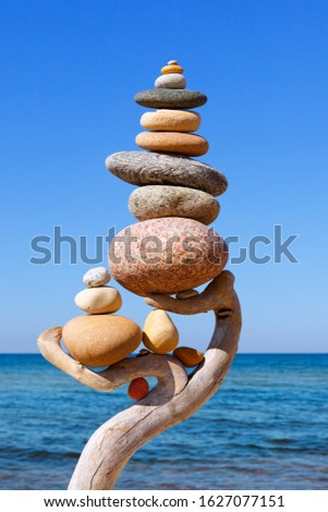 Multicolored balanced stones on an wooden snags, on a blue sky and sea background. Concept of harmony, balance and meditation #1627077151