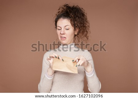 Negative human reaction, feelings, attitude. Shot of disgusted squeamish Caucasian female in casual wear grimacing, sticking out tongue, feeling nauseous because of bad smell or stink from envelope. #1627102096