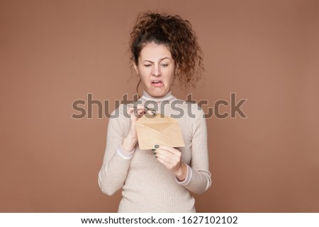 Negative human reaction, feelings, attitude. Shot of disgusted squeamish Caucasian female in casual wear grimacing, sticking out tongue, feeling nauseous because of bad smell or stink from envelope. #1627102102