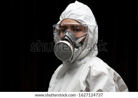 Woman wearing gloves with biohazard chemical protective suit and mask. Royalty-Free Stock Photo #1627124737