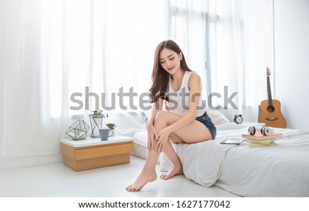 Portrait of beauty  smiling asian woman applying a lotion to her leg skin during her morning routine. Cute asian girl. Skincare body lotion, beauty clinic skincare spa indoors woman lifestyle concept #1627177042