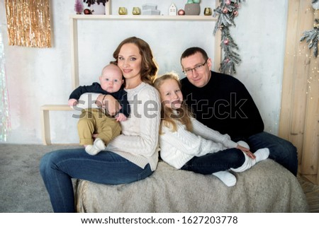 Happy mom and dad, sister and little brother on the bed in a large bright bedroom. decor and lights. Big happy family. The concept of parental love and parenting. #1627203778
