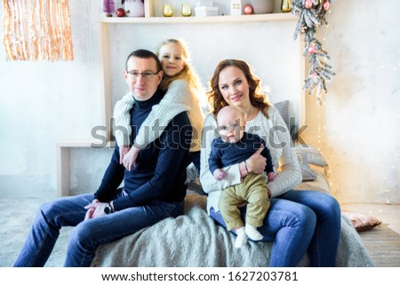 Happy mom and dad, sister and little brother on the bed in a large bright bedroom. Christmas decor and lights. Big happy family. The concept of parental love and parenting. #1627203781
