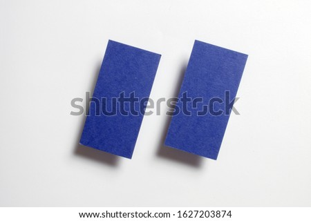 Two blue blank matt textured business cards flying and isolated on white paper background, us standard size 3.5 x 2 inches,  studio photo.