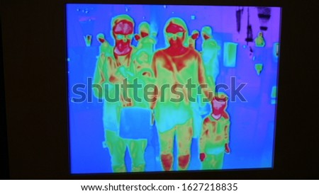 View from the thermal imaging camera - coronavirus - temperature, two adults and a child, visible temperature of their bodies marked with colors. Virus pandemic and epidemic.