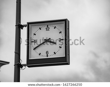 Street clock with a traditional dial and hands arrows for hours and minutes. An rectangular boxed analog clock on a city lighting pole shows the exact time 3:40 pm. Black and white shot