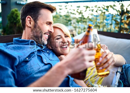 Picture of happy couple resting on patio together during summer day with beer and popcorn