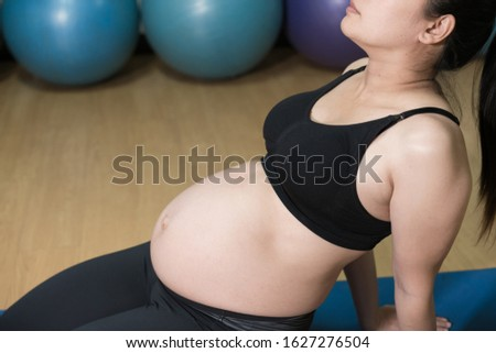 healthy pregnant woman doing yoga in gym. Working out, yoga and fitness, pregnancy concept