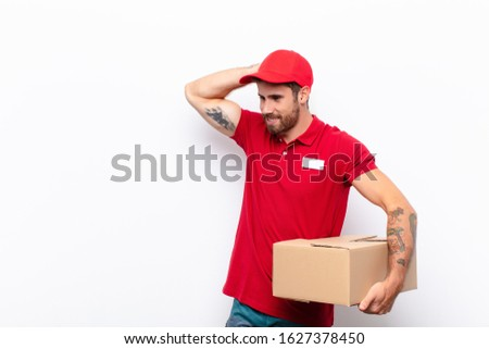 smiling cheerfully and casually, taking hand to head with a positive, happy and confident look. delivery concept #1627378450