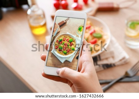 Female food photographer with mobile phone taking picture of pasta