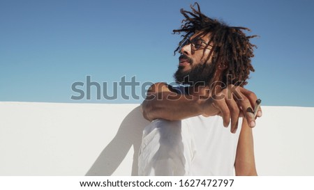 Black man smoking weed at the rooftop with blue sky at background