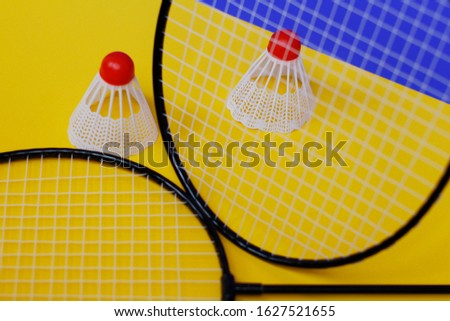 Badminton. Two shuttlecocks and two badminton racket. The colored background is blue and yellow. Idea for a magazine. #1627521655