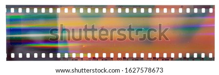 Start of 35mm negative filmstrip, first frame on white background, real scan of film material with cool scanning light interferences on the material. Royalty-Free Stock Photo #1627578673