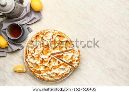 Tasty lemon pie with tea on table