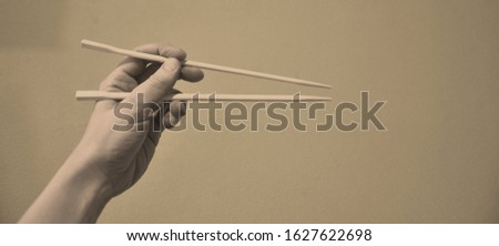 Chinese chopsticks in hand, photo in restrained colors, sepia color #1627622698