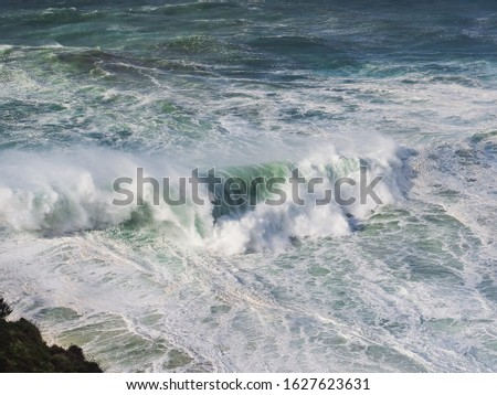 Breaking grand wave in the North Beach of Nazaré or Silver Coast in Portugal, Europe. Stormy Atlantic ocean. Top view. Scenic, powerful, foamy wave in phenomenal underwater canyon, popular surf route. #1627623631