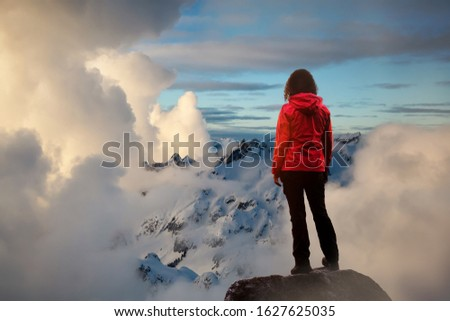 Adventurous Girl watching the Beautiful Dramatic Sunset on top of the Mountains. Composite Image with Landscape taken in BC, Canada. Concept: Adventure, Art, Travel, Hike, Outdoors, Sport, Explore #1627625035