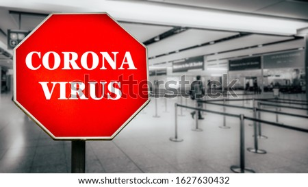 Coronavirus written on stop sign with passengers arriving at passport control within generic airport. #1627630432
