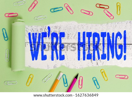Handwriting text writing We Re Hiring. Concept meaning recently employ someone or pay him to do particular job Stationary and torn cardboard placed above a wooden classic table backdrop. #1627636849