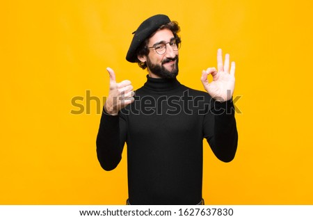 young french artist man feeling happy, amazed, satisfied and surprised, showing okay and thumbs up gestures, smiling against orange wall
