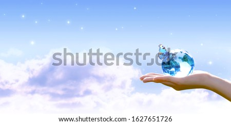 Card for World Earth Day. Clean air, Ozone Day concept. Saving environment, save and protect green planet and ecology. Earth crystal globe in human hand and butterfly on stars blue sky background.