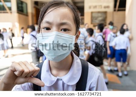 Asian child girl student thumbs down wearing medical face mask in school,epidemic,Coronavirus,MERS-CoV,air contamination,Wuhan coronavirus 2019-nCoV,concept of Corona virus quarantine,Covid-19 Royalty-Free Stock Photo #1627734721