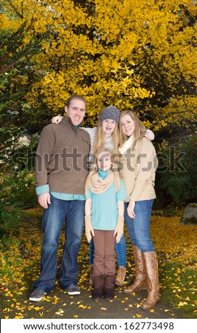 Vertical photo of family all holding each other during a break from a walk in the park during the autumn season